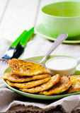 Vegetable marrows fritters with sour cream on a green plate. Royalty Free Stock Photo