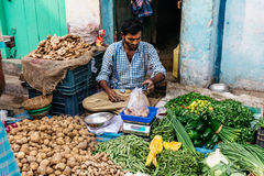 Vegetable merchant sell potato that weigh by digital scales in the morning market in Kolkata, India Royalty Free Stock Images