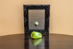 Vegetable in the mirror. Looking at the future. Pepper on a table stock image