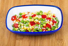 Vegetable mix in blue bowl on bamboo board Stock Image