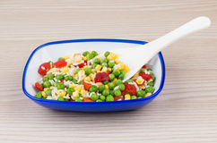 Vegetable mix in blue bowl on table and plastic spoon Royalty Free Stock Photo