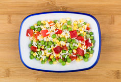 Vegetable mix in blue bowl on wooden bamboo board Royalty Free Stock Photography