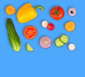Vegetable mix on blue isolated background. Fresh yellow pepper, chopped tomatoes, onion, round cucumber slice, carrot, radish. The concept of a healthy royalty free stock photos