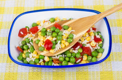 Vegetable mix in bowl and spoon on plaid tablecloth Stock Photo