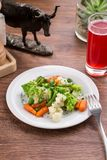 Vegetable mix with carrot, romanesco and cauliflower and berry drink on wooden table. Side view royalty free stock images