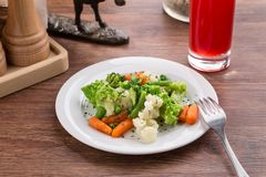 Vegetable mix with carrot, romanesco and cauliflower and berry drink on wooden table. Side view stock photo