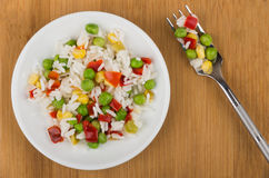 Vegetable mix on plate and fork on wooden table Stock Photo