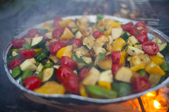 Vegetable mix prepared on a grill. With fire and smoke in a background Royalty Free Stock Photos