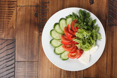 Vegetable mix. (salad, cucumber, tomato, parsley) and cheese on a white plate. wooden background Stock Images