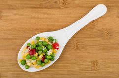 Vegetable mix in white plastic spoon on wooden bamboo board Stock Image