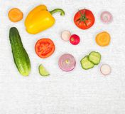 Vegetable mix on white wooden isolated background. Fresh yellow pepper, chopped tomatoes, onion, cucumber slice, carrot, radish. The concept of a healthy stock photography