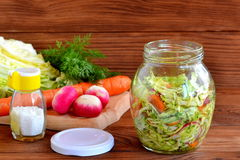 Vegetable mixed salad in a jar. Salad prepared of radish, carrots, cabbage, olive oil, salt and dill Royalty Free Stock Photos