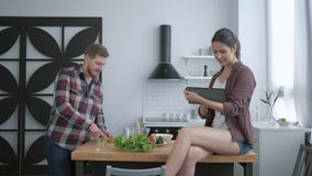 Vegetable nutrition diet, bearded man prepares delicious healthy salad from fresh vegetables and greens and woman sits. On table with tablet in hand and talks stock video footage