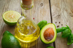 Vegetable oil, avocado, lime and basil on old wooden background Royalty Free Stock Images