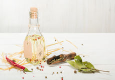 Vegetable oil in a bottle with seasonings and spices on a white wooden background. Stock Photo