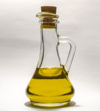 Vegetable oil in a transparent bottle decanter with stopper on a white background. Vegetable oil in a transparent bottle decanter with stopper Royalty Free Stock Image