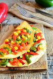 Vegetable omelet on a wooden board. Delicious fried omelet stuffed with red and green bell peppers and corn Stock Image