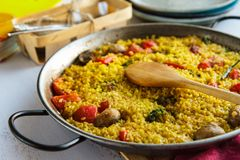 Vegetable paella cooked in a frying pan close-up. Horizontal Stock Image