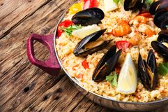 Paella with seafood. Vegetable paella with seafood on wooden background Royalty Free Stock Photography