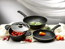 Vegetable into pans and pot. Some broccoli, tomatoes and peppers are into a nonstick wok, pan and pot, other are on the table Royalty Free Stock Photos
