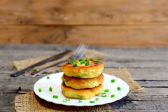 Vegetable patties on a plate, fork, knife on wooden table. Fried patties cooked of potatoes, green peas, carrot and green beans Royalty Free Stock Image