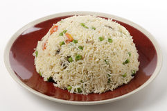 Vegetable pilau. A moulded dome of vegetable pilau rice on a plate ready for serving, made with garlic, sliced mushrooms, chopped tomato, cumin seeds and basmati Stock Photos