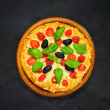 Vegetable Pizza on Dark Background. Top View of Vegetable Pizza with Olives, Basil and Tomatoes Stock Photos