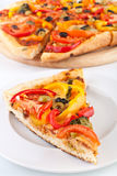 Vegetable pizza slice, pizza at the back Stock Image
