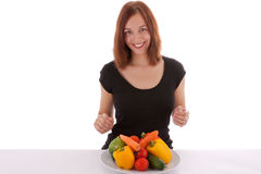 The vegetable plate. A young woman looks at a plate of vegetables Royalty Free Stock Photo