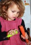 Vegetable Preparation. Little girl preparing dinner, peeling carots Royalty Free Stock Photos