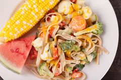 Vegetable Primavera with watermelon and corn up close top view. Vegetable Primavera with white sauce and shredded cheese with corn on the cob and slice of Royalty Free Stock Photography