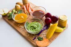 Vegetable puree or baby food in glass bowls. Baby food, healthy eating and nutrition concept - vegetable or fruit puree in glass bowls and feeding spoon on Stock Images