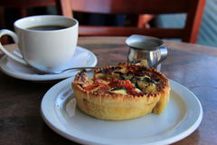 Vegetable quiche and hot cup of coffee Royalty Free Stock Images