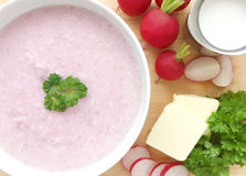 Vegetable radish soup. Cream radish soup surrounded by ingredients - radishes, butter, cream and green parsley. Wooden background. Top view Stock Images