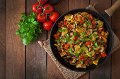 Vegetable Ratatouille in frying pan. On a wooden table Stock Photos