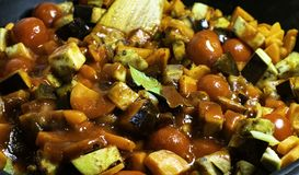 Braised zucchini, eggplant, hot pepper, tomato paste, bay leaf, carrot, tomatoes, and dill in pan with wooden spatulas. Dietary cu stock photo