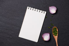 Vegetable recipe. Open menu book with fresh herbs and spices on. Dark background Stock Photo
