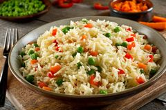 Vegetable Rice Pilaf. Delicious vegetable rice pilaf with green peas, carrots and red peppers stock photo