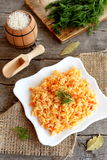 Vegetable risotto on a plate, dill sprigs, cutting board, spoon on old wooden background. Simple vegetarian rice dish Royalty Free Stock Images