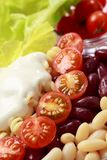 Vegetable salad. Close-up. White and red bean, cherry tomatoes, pasta, lettuce and cream Royalty Free Stock Images