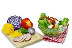 Vegetable salad in a bowl. Vegetable salad with white cheese, ham and ingredients on chopping board, isolated on white royalty free stock photo