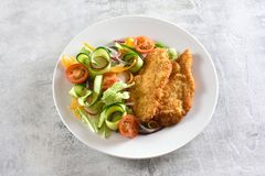 Vegetable salad and breaded chicken breast stock images