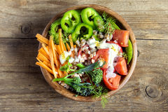 Vegetable salad with buckwheat. Fresh organic vegetable salad with buckwheat over rustic wooden background with copy space Royalty Free Stock Photos