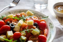 Vegetable salad with cheese and a glass of water stock image