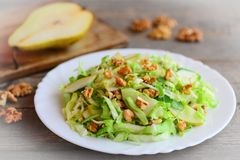 Home cabbage slaw with pear and walnuts. Healthy pear and cabbage slaw on a plate. Great food for getting vitamins. Closeup Royalty Free Stock Images