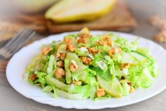 Homemade cabbage slaw with pear and walnuts. Easy pear and cabbage slaw on a plate. Food highest in vitamins. Closeup Stock Images