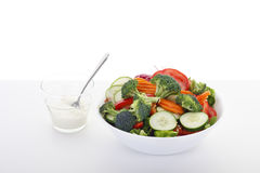 Vegetable Salad with Dressing on White Table Stock Photos