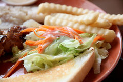 Vegetable salad with french fries and toast on dish. Stock Photography