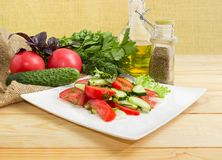Salad with tomatoes, cucumbers and some ingredients for its prep. Vegetable salad with fresh sliced tomatoes and cucumbers and greens on square white dish and stock photography