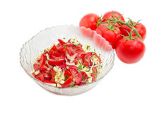 Tomatoes salad against cluster of the fresh tomatoes. Vegetable salad of the fresh sliced tomatoes, white bell pepper, onion and potherb in a glass salad bowl Stock Photos